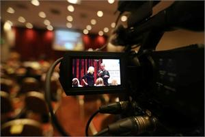 Image of a video camera recording two presenters from Spectronics talking to the seated crowd of delegates.