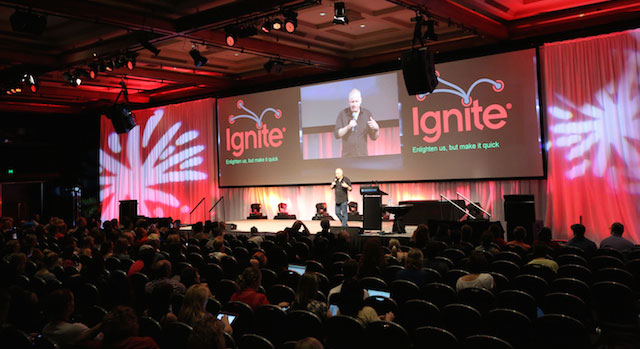 Ignite Session in progress with Master of Ceremonies Derek Austin up on stage in front of a large seated crowd