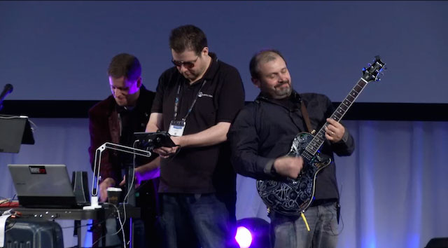 Three presenters up on stage playing guitar, and electronic musical instruments