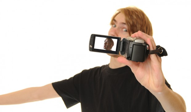 Photo of a guy video-ing himself with a small video camera